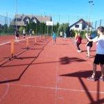 Chłopak przygotowuje się do serisu sposobem dolnym, w tle grupa gra w mini tenisa