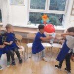 chłopcy pompują balona gazem z butelki