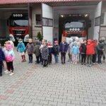 dzieci stojące przed strażą pożarną, przed wozami strażackimi