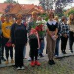 Uczniowie stoją przed pominkiem z kwiatami