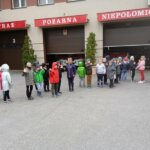 zadowolone i machające dzieci przed remizą strażacką