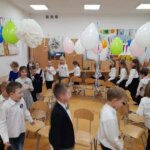 Uśmiechnięte dzieci tańczące w klasie przystrojonej balonami i serpentynami