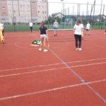 Dziewczyna i chłopak grają w mini tenisa, a obok koleżanka przygląda się ich wyczynom