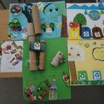 Prace plastyczne uczniów zawierające zadowoloną Ziemię i kosze do segregacji śmieci