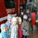 uśmiechnięte dzieci oglądają stroje strażaków