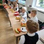 Uczniowie ubrani odświętnie siedzący przy stolikach jedzą posiłek