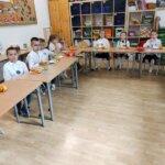 Zadowolone dziewczynki i chłopcy ubrani na galowo spożywają poczęstunek